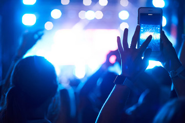Crowd of audience with hands using camera phone to take pictures and videos at live concert, smartphone records live music festival.