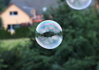 A one big bubble flying in the air. Bubble serve as mirror so we can see some house and cloudy. Bubble is mainly created from green and purple colour