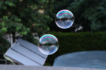 A two bubbles flying in the air above swimming pool and garden. Colourful and both show us our house. Effect mirroring is here.