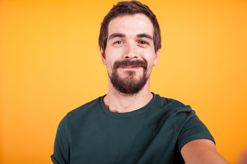 Close up selfie portrait of happy smiling man isolated on yellow background