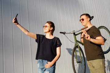 Cheerful friends having fun together. Pretty girl takes a selfie on smartphone, standing with happy guy, holding a bike on his shoulder and showing peace sign. Outdoors.