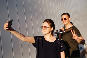 Young happy couple takes a selfie on smartphone, cheerfully smiling, while guy holding a bike, wearing sunglasses. Summertime.