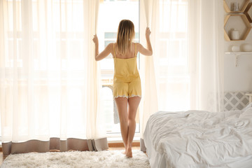 Beautiful young woman opening curtains in morning