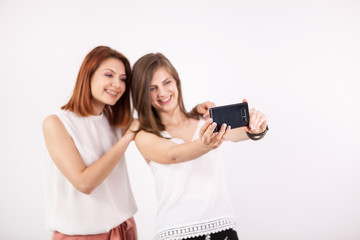 Portrait of two gorgeous young woman, a redhair and a brown-haired, taking a selfie over a white wall in studio