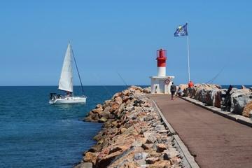 Canet-en-Roussillon, voilier naviguant au large du phare au bout de la jetée (France)