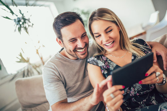 Attractive happy married couple using digital tablet at home.