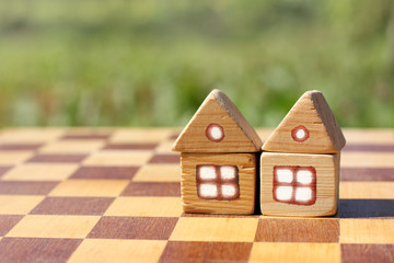 Plot for play together in life/ Two small wooden house on a chessboard