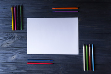 Palette of multicolored pencils and the sheet of white paper on dark blue wooden desk.