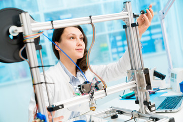 Young woman in lab adjust 3d printer
