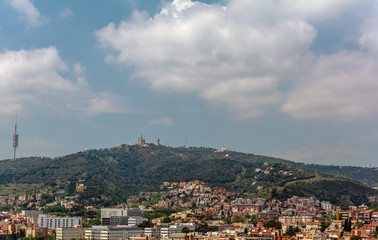 View to the Tibidabo mountain with Sagrat Cor church and Amusement Park atop. The Torre de Collserola telecommunications tower is to the left. All three are prominently visible from most of the city.