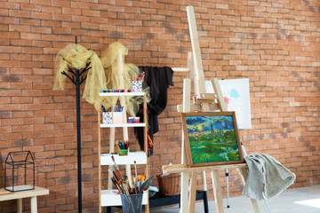 Easel with beautiful picture in artist's workshop