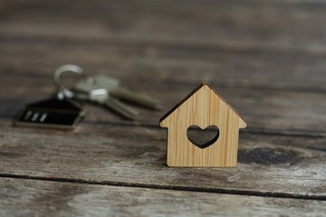 House keys with wooden home keying on wood table, copy space, property concept