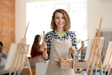 Female artist with tools and paints in workshop