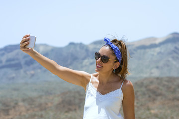 Beautiful woman doing a selfie on top of a mountain, with beautiful views of the vicinity of the teide behind her, looking fixedly at the mobil.