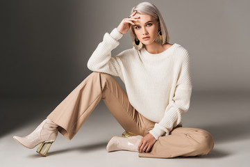 attractive fashionable woman posing in white trendy sweater, beige pants and autumn heels, on grey Wall mural