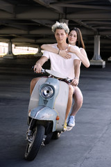 young beautiful couple in love riding on old scooter. adventure and vacations concept. motorbike, summer, traveling, romance, smiling, happy, having fun, stylish outfit, date, enjoying in trip