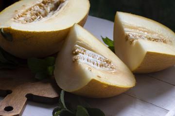 juicy ripe yellow melon cut on a wooden board