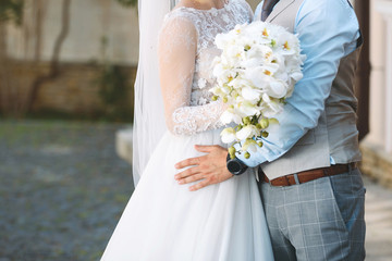 Groom Hugging Bride with Bouquet