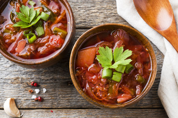 Borsch, beet soup in a wooden bowl with fresh herbs on a wooden background