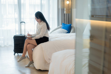Close up of a happy beautiful Asian business woman smiling cheerfully resting at her hotel suite during business trip making notes and thinking strategy planning time management.