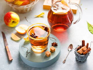 Apple cider drink, hot cocktail with cinnamon sticks and apple slices. Tea with spices. Autumn sunny cozy morning mood. Romantic atmosphere.