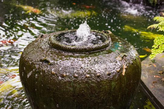 Jar fountain decoration in the green garden.Thailand.