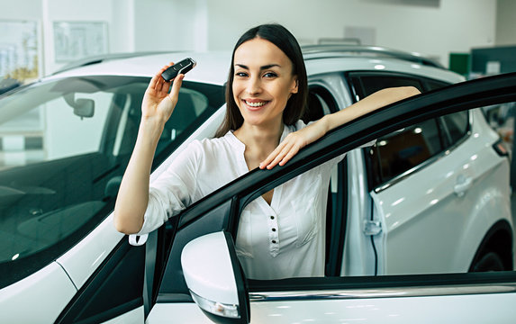 Beautiful woman buying a new car for job and travel in dealership, girl customer