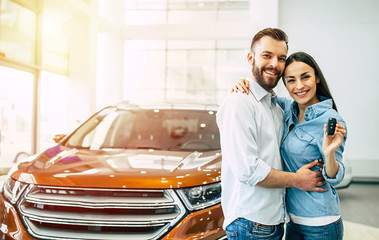 Visit the dealership. Happy young couple chooses and buying a new red car for the family.