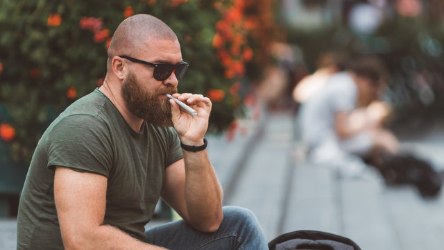 Young man is sitting in the park in Amsterdam (Holland/Netherlands) and smoking cannabis or weed joint in his left hand.