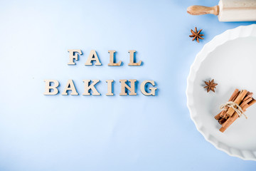 Baking concept with white baking dish, rolling pin, spice for baking, on a light blue background, top view copy space