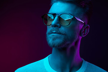 Neon studio portrait of serious man model with mustaches and beard in sunglasses and white t-shirt