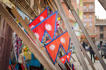 Souvenir shop selling Nepal flags under wooden scaffoldings supporting an earthquake damaged house, Bakhtapur, Nepal.