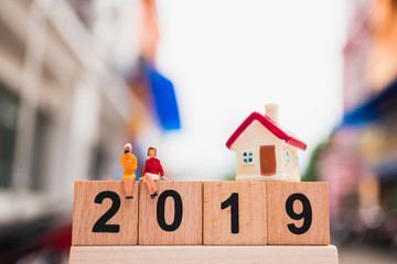 Miniature people, couple woman sitting on wooden block 2019 with mini house using as business, social and property concept