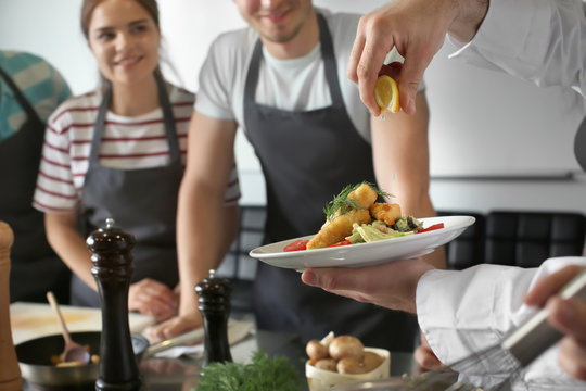 Male chef holding plate with prepared dish during cooking classes