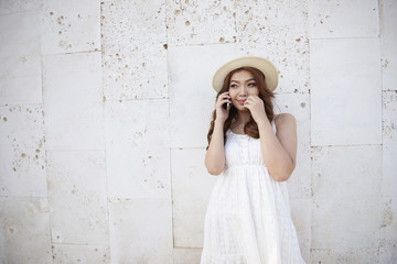 Asian woman talking on the phone on a white background portrait standing outdoors. Pretty young woman in hat and dress using mobile phone on city street urban background. Happy emotional hipster girl