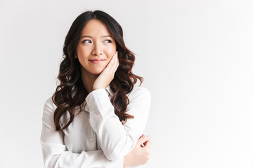 Portrait of happy chinese woman with long dark hair looking aside at copyspace and touching cheek, isolated over white background in studio
