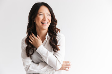 Image of charming chinese woman with long dark hair looking aside at copyspace and laughing, isolated over white background in studio