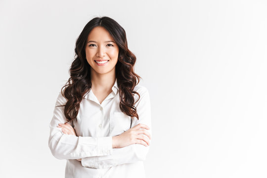 Portrait of gorgeous asian woman with long dark hair looking at camera with beautiful smile and arms crossed, isolated over white background in studio