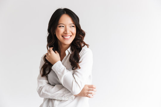 Photo of optimistic asian woman with long dark hair looking aside at copyspace and laughing, isolated over white background in studio