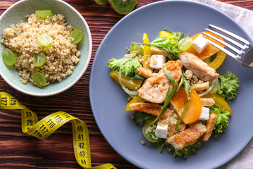 Tasty chicken salad with vegetables and measuring tape on wooden table. Diet food
