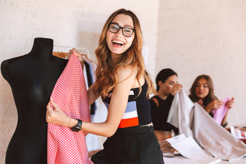 Happy young woman clothes designer at the atelier