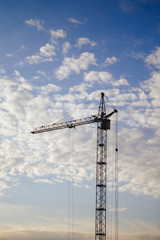 construction tower crane against blue sky with clouds