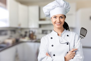 Portrait of young woman chef on background