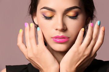 Beautiful young woman with professional manicure on color background, closeup
