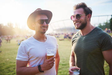 Two young male friends with glasses of beer at Holi Festival
