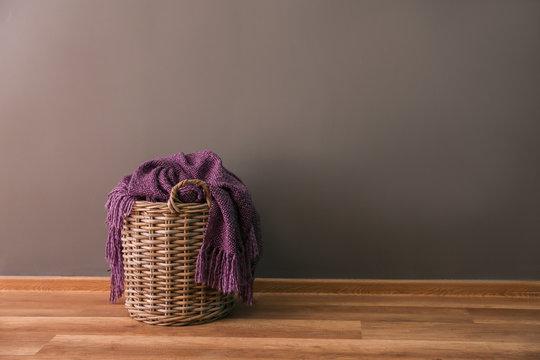 Wicker basket near grey wall