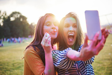 Two young woman covered in coloured chalk powder taking selfie at Holi Festival