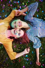 Two young women covered in coloured chalk powder lying on grass at Holi Festival, overhead portrait