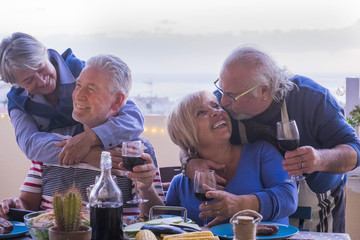 causasian mature couples friends having fun during evening dinner together. kiss and hug and smile and laugh for great retired lifestyle concept. outdoor on the terrace with ocean view.