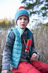 Boy in knitted hat sitting on bench in reeds, portrait